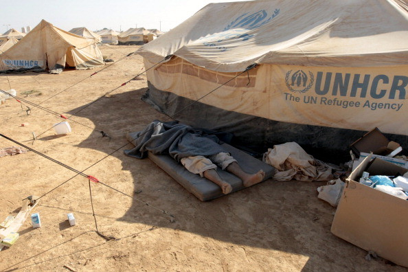 TO GO WITH AFP STORY BY KAMAL TAHA A Syrian man sleeps outside his UNHCR tent at the Zaatari camp for Syrian refugees, outside the northern Jordanian city of Mafraq, on August 12, 2012. French military medics delivered aid to the camp a day after they arrived on a French cargo plane carrying tonnes of supplies and medical equipment to help tens of thousands of Syrians who fled their country's violence. AFP PHOTO/KHALIL MAZRAAWI        (Photo credit should read KHALIL MAZRAAWI/AFP/GettyImages)