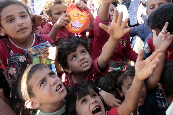 Syrian refugee children receive toys and other goodies distributed by an aid organization at at the Zaatari refugee camp close to the northern Jordanian city of Mafraq, near the border with Syria, on the first day of the Eid al-Fitr, marking the end of the holy month of Ramadan, on August 19, 2012. Around  3,000 Syrians are taking shelters in the refugee camp that was opened last month to alleviate the humanitarian crisis in Syria.  AFP PHOTO/KHALIL MAZRAAWI        (Photo credit should read KHALIL MAZRAAWI/AFP/GettyImages)